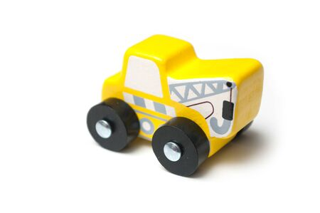 Closeup of miniature toy, wooden yellow tow truck on white background