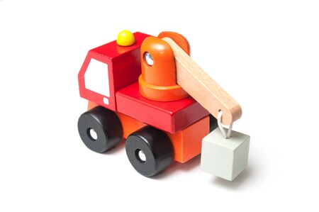 Closeup of miniature toy, wooden red truck with carrycot on white background