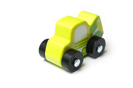 Closeup of miniature toy, wooden green car on white background Фото со стока