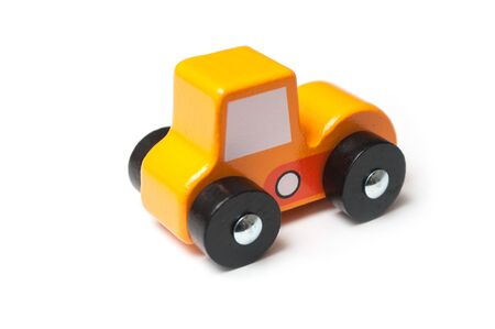 Closeup of miniature toy, wooden orange color car on white background