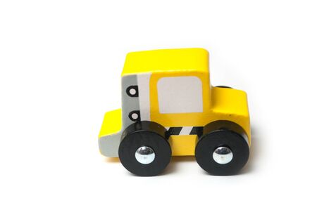 Closeup of miniature toy, wooden yellow car on white background Stock fotó