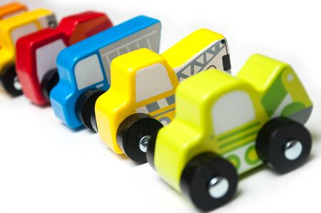 Closeup of miniature toys alignment colorful wooden cars and trucks on white background Zdjęcie Seryjne