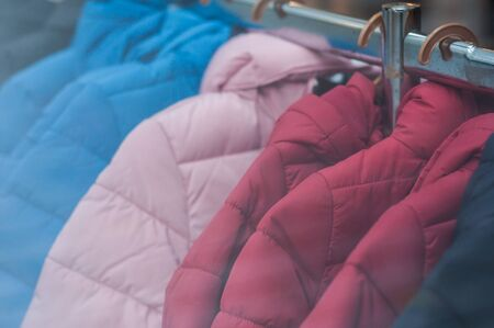Closeup of colorful winter jackets on hangers in fashion store showroom