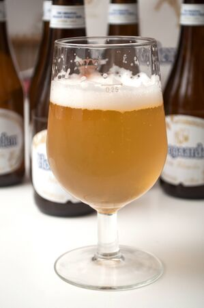 Mulhouse - France - 25 November 2019 - Closeup of the famous belgian Hoegaarden of white bier in glass on bottles background 新聞圖片