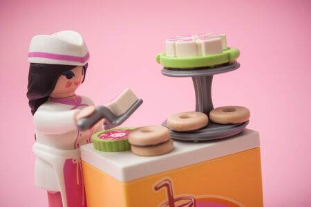 Mulhouse - France - 26 November 2019 - Closeup of PLaymobil figurine with pastry costume on pink background
