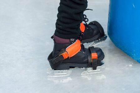 Closeup of feet of children with ice skates on an ice rink