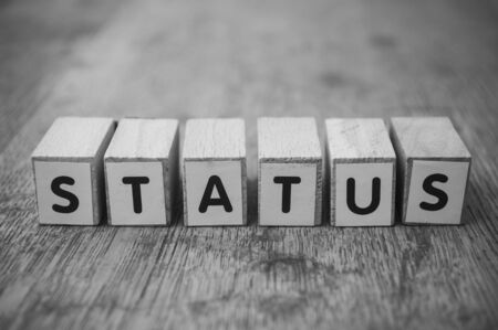 closeup  of wooden word on wooden table background concept  - Status  Banco de Imagens