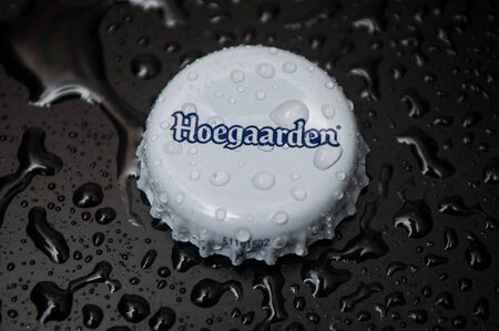 Mulhouse - France - 30 November 2019 - Closeup of  drops of water on metallic cap of bier by Hoegaarden brand on black background