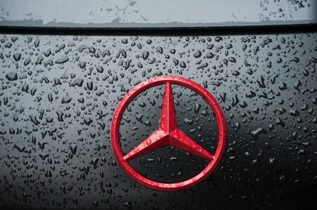 Mulhouse - France - 1 December 2019 - Closeup of rain drops on red logo on black Mercedes parked in the street Redactioneel