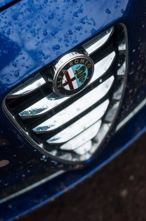 Mulhouse - France - 1 December 2019 - Closeup of rain drops on blue alfa romeo front parked in the street