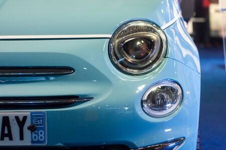 Mulhouse - France - 1 December 2019 - Closeup of front light of blue Fiat 500 pared in a exposition showroom