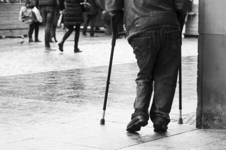 Closeup of disabled man walking with sticks in the street