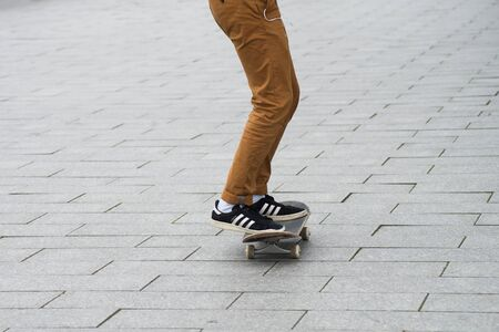 Mulhouse - France - 31 January 2020 - Closeup of skater legs wearing black sneakers by Adidas rolling on skate board in the street