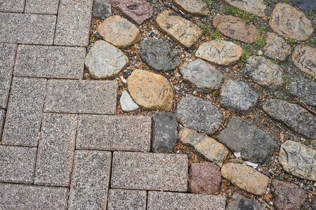 Closeup of modern concrete cobbles and vintage granit cobbles texture