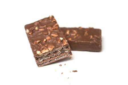 Closeup of crunched chocolate bar with nuts on white background