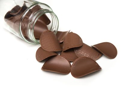 Closeup of chocolate in shaped tiles falling from a glass container on white background Stockfoto