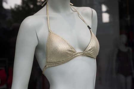 closeup of golden bikini on mannequin in fashion store showroom for women