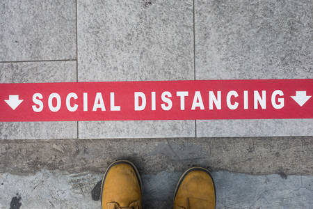 Closeup of feet standing on the pavement behind the red line - Social Distancing  concept Stock Photo