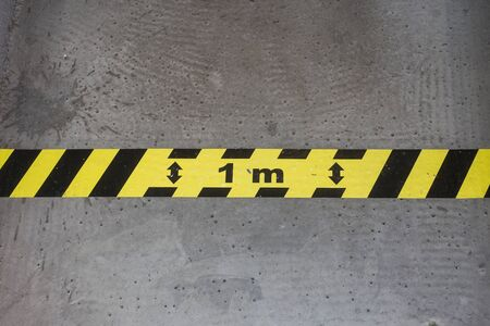 Closeup of yellow and black stripped line on the floor - Social distancing line