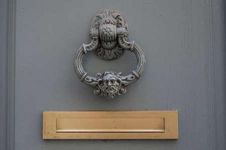 Closeup of vintage knocker on wooden door
