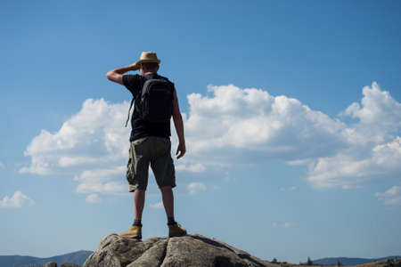 Portait of man with backpack standing on the rocks at the top of the mountain on blue cloudy sky background