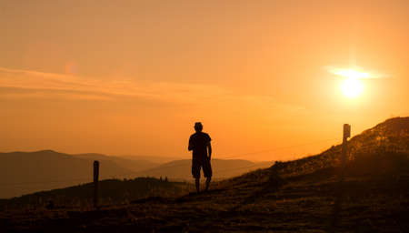 Portrait of man silhouette standing at the top of the mountain looking the landscape on sunset background Фото со стока