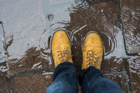 Closeup of feet of man wearing leather boots standing in a puddle of water in the street