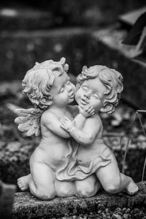 Closeup of stoned angels kissing on tomb in a cemetery