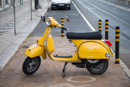 Lisbon - Portugal - 30 September 2020 - View of yellow vintage vespa scooter parked in the street 新聞圖片