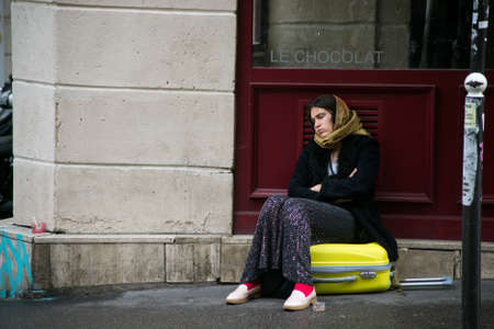 Paris - France - 25 October2020 - Portrait of poor gipsy woman sitting on a suitcase in the street