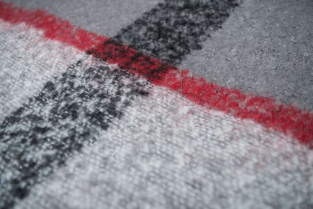 Closeup of red, black and grey woolen scarf texture Фото со стока