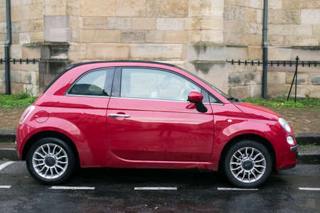 mulhouse - France - 6 December 2020 - Profile view of red Fiat 500 parked in the street by rainy day Redakční