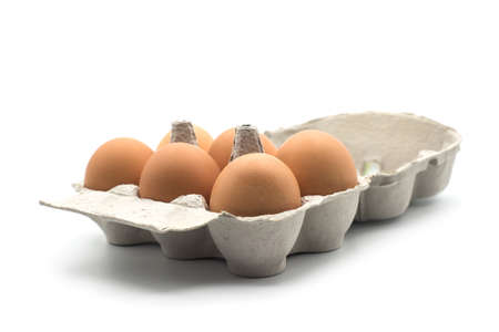 Closeup of organic eggs in a grey carton box on white background