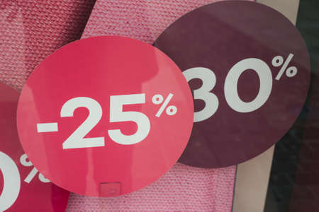 Closeup of discount sign -25% and -30 % in a fashion store showroom