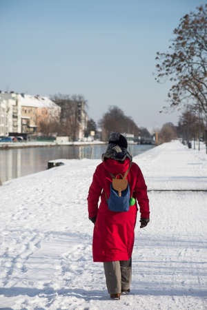 Portrait on back view of woman walking in border the frozen river wearing a winter red  coat