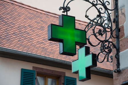 Closeup of green pharmacy signage on stoned building facade in the street