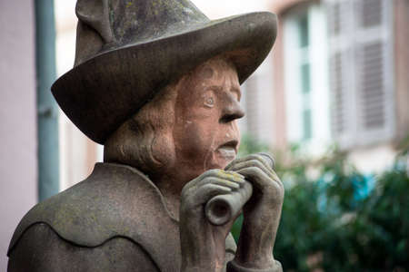 Closeup of ancient statue of musician playng with flute  in the village of Ribauville in France Stockfoto