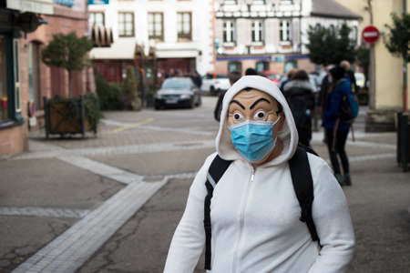 Ribauville - France - 18 February 2021 - Portrait of teenager with of casa de palel, the famous serie tv on netflix and medical mask walking in the street Redactioneel