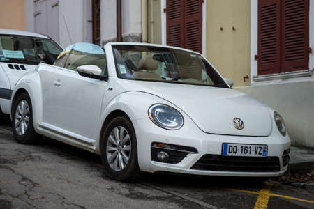 Ferrette - France - 20 February 2021 - Front view of white Volkswagen bettle convertible parked in the street