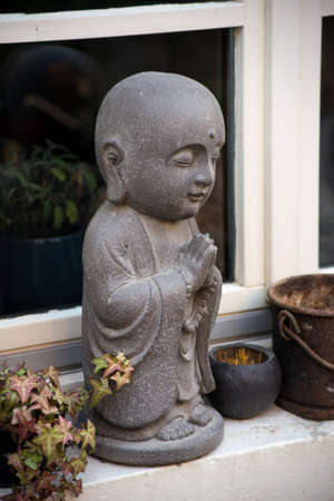 Closeup of stoned little buddha at the window of house in the street