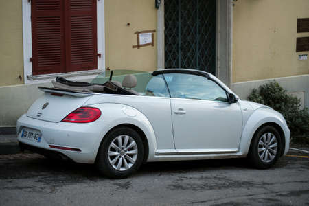 Ferrette - France - 20 February 2021 - Profile view of white Volkswagen bettle convertible parked in the street