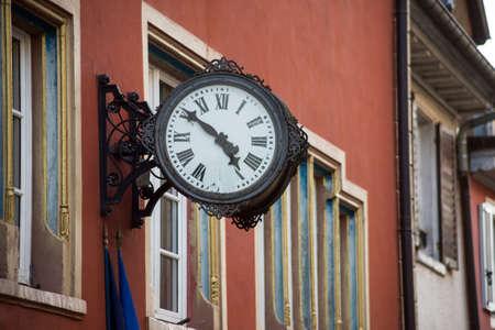Closeup of retro clock on building facade in the street