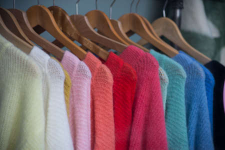 Closeup of colorful woolen pullover on hangers in a fashion tore showroom