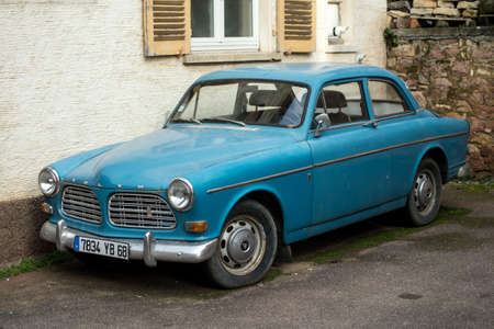 Eguisheim - France - 22 February 2021 - Front view of blue vintage Volvo Amazon 1966 car parked in the street of alsatian village