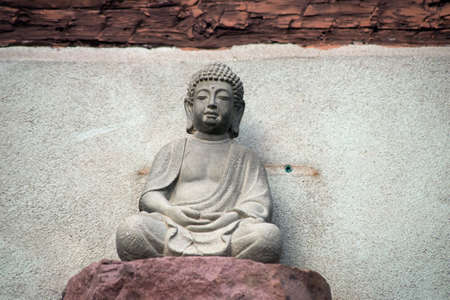 Closeup of stoned little buddha on  building facade of house in the street Stockfoto