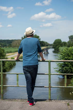 Portrait on back view of man standing on bridge on wthe water looking the rural landscape Stock Photo