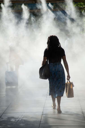 Portrait of people walking in urban park in sprayer installation