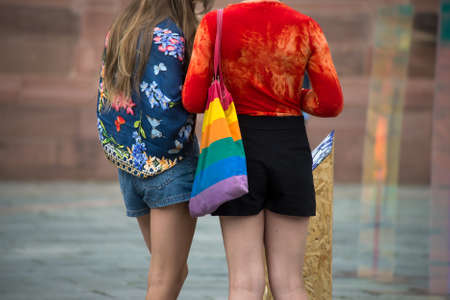Closeup of lesbian girls standing in the street with rainbow bag