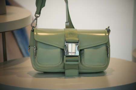 Strasbourg - France - 11 Jully 2021 - Closeup of green color handbags by Prada in a luxury fashion store showroom