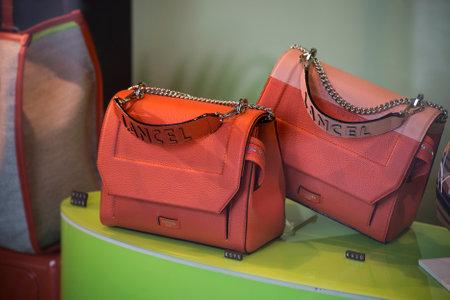 Strasbourg - France - 11 Jully 2021 - Closeup of orange color handbags by Lancel in aluxury fashion store showroom Editorial